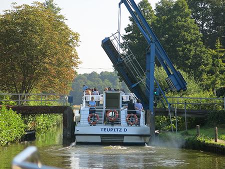 Fahrgastschiff fährt auf einem Kanaldurch eine enge geöffnete Klappbrücke, durch es gerade hindurchpasst